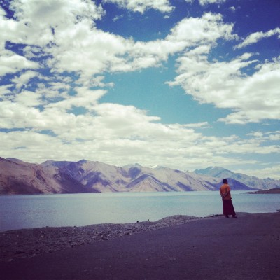 A monk by Pangong Lake in the Ladakh mountains, India